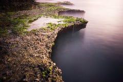 Morning at the sea. A morning at a cliff covered in green moss at Phan Rang, Vietnam Royalty Free Stock Photos