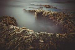 Morning at the sea. A morning at a cliff covered in green moss at Phan Rang, Vietnam Royalty Free Stock Photo