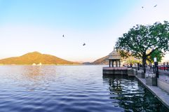 Morning shot of Fateh sagar lake with blue water and hills in th. Morning shots of the fateh sagar lake with blue water, a walkway and beautiful hills in the Stock Photography