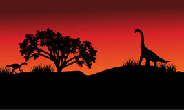 At morning silhouette eoraptor and brachiosaurus Royalty Free Stock Image