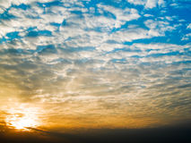 Morning Skies. Sun breaking out above low altitude clouds and illuminating the undersides of the mid altitude altocumulus clouds while at high altitude the skies Stock Images
