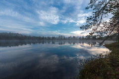 Morning sky and clouds reflected in a small pond Stock Photography