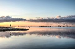 Morning sky reflecting in the estuary. Blue sky with a few clouds in the distance reflecting in the calm water of Haringvliet estuary near the island of Hoekse Stock Photo