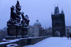 Morning snowy Prague Old Town with Bridge Tower and St. Francis of Assisi Cathedral from Charles Bridge with its baroque Statues Stock Image