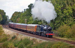 Morning steam. Steam train and carriages pass along a preserved railway line taking passengers on short pleasure trips Stock Photography
