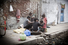 Morning on a street, poor indian family. At November 10, 2013 in Old Delhi, India. Indian capital still uses man powered rickshaws as a usual mean of transport Stock Photos