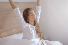 Morning stretch on the bed by the window at home royalty free stock images