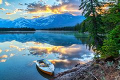 Morning Sunrise Over Edith Lake in Jasper National Park. Morning sun breaks out over the Rocky Mountains at Edith Lake in Jasper National Park, with a boat in stock image