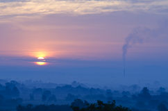Purple morning. Morning sun in the field with chimney of old factory Stock Image