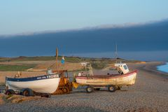 Morning Sun on  Fishing Boats on a Shingle Beach. Fishing boats Anna Gail and Lady Iris catch the early morning sun. The shingle beach at Weybourne on the North Stock Photos