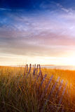 Morning sun on old fence and dunes Royalty Free Stock Photos