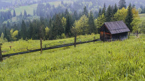Morning sun rays in the fog mountains house. Early morning sun rays illuminate the dawn beautiful Carpathian landscape in the mist on the background of ancient Royalty Free Stock Images