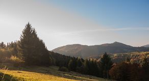 Morning sun rays in the fog mountains house. Early morning sun rays illuminate the dawn beautiful Carpathian landscape in the mist on the background of ancient Royalty Free Stock Photo