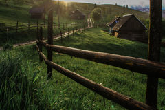 Morning sun rays in the fog mountains house. Early morning sun rays illuminate the dawn beautiful Carpathian landscape in the mist on the background of ancient Stock Photography