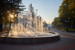 Morning sun rays in a fountain in the alley. Ancient church on the background royalty free stock photo