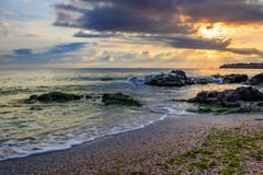 Morning sun rays illuminate sandy beach with small rocks Royalty Free Stock Photo
