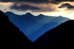 Morning sun rays over a steep valley and peaks of Gailtal Alps. Sun rays of the rising sun reach steep, forested valley in Plocken Pass and Torkofel, Mittelkofer Stock Images