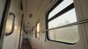 The morning sun shines through the windows of the passenger train car. The interior of the car, a number of windows and. In the train car, a long corridor with a stock footage