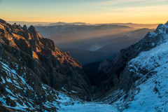 Morning sunbeams penetrate fog and illuminate rocks. Rocks and snow in foreground. Yellow and blue sky in background.  Morning sunbeams penetrate fog and Royalty Free Stock Image