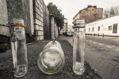 3 empty abandoned small alcohol bottles on the empty street in W royalty free stock photo