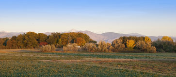 Morning Sunlight. Early morning sunlight shines on a plowed field and farm with distant trees and mountains, on the Colorado prairie.  A trailer or caravan can Royalty Free Stock Photo