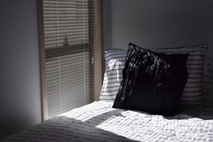 Morning sunlight on the bed. The morning sunlight cast on a modern bed from the open blinds Stock Photo