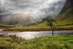 Morning sunlight breaks through rain clouds at Glen Etive, Glencoe. The morning sun breaks through the rain clouds and light rain to shine down on part of the stock photography