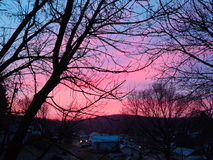 Morning sunrise. Beautiful bright pink and blue morning sunrise above a small town on a cool morning Royalty Free Stock Photography