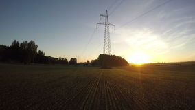 Morning sunrise on farmland field with electric tower, timelapse 4k stock video