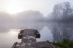 Sunrise sunbeams penetrating through the fog above the lake with wooden pier. Morning sunrise fog above forest lake and pier stock photography