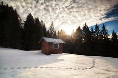 Morning sunrise over cabin in winter alpine forest Royalty Free Stock Images