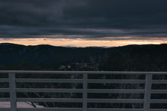 Morning sunrise over the distant mountains from ski lodge balcon. Dramatic sunrise with storm clouds rolling in from the balcony of ski lodge in Mount Buller Royalty Free Stock Images
