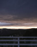 Morning sunrise over the distant mountains from ski lodge balcon. Dramatic sunrise with storm clouds rolling in from the balcony of ski lodge in Mount Buller Royalty Free Stock Photography