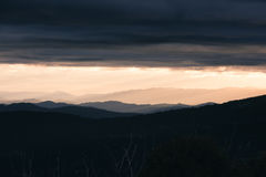 Morning sunrise over the distant mountains. Sun rising over the mountains in Mount Buller, Victoria Australia. Colourful sky with silhouettes of mountains in the Royalty Free Stock Photography