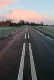 Morning sunrise over a wet road. Morning sunrise over an empty and wet road with white paint lines through the field near a town in Utrecht Royalty Free Stock Photos