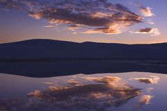 A morning sunrise reflects in a pool of rainwater in White Sands National Monument. stock photo