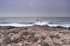 Morning sunrise on rocky sea coast, lit by the moon stock image