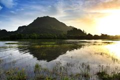 Morning sunrise at Tasoh Lake, Perlis, Malaysia. This is a sunrise shot of tasoh Lake at perlis, Malaysia. The lake is calm and reflection of the mountain can be Royalty Free Stock Image