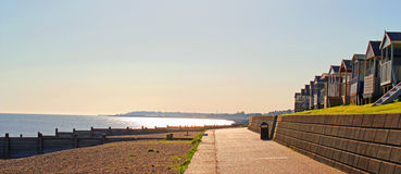 Morning Sunshine. This photo shows the early morning Spring sunshine glistening on the water at Whitstable beach while the beach huts look on Stock Photography