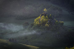 Morning sunshine with fog over a mountain landscape with rocks and trees in direct sunlight. Fundatura Ponorului, Romania Stock Images