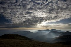 Morning sunshine piercing the clouds. Beautiful morning sunshine piercing the cirrus clouds in mountains and fog on valleys Stock Images
