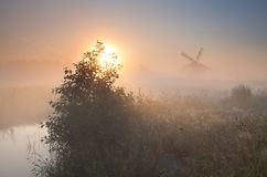 Morning sunshine and windmill in dense fog Royalty Free Stock Photography