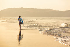 Morning surf. Young girl walking along the beach in the morning stock photos