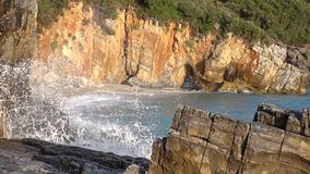 Morning Surf on the Rocky Beach. Slow Motion. Rocky seashore. Small beach with stone arch. Summer morning. Waves breaking on stones with lots of splashes. Slow stock footage