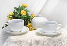 Morning table. The wall in the background is a light off-white. Bowl on table is empty, suggesting the food has yet to arrive.White cups on a white table, a royalty free stock image