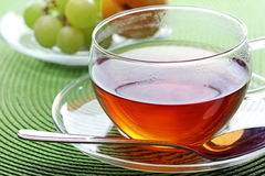 The morning tea. The closeup of the cup of tea with a silver spoon Stock Photography