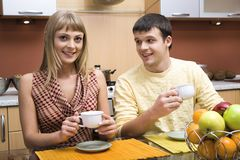Morning tea. Pretty woman and smiling man drink the tea at the table in the kitchen Royalty Free Stock Photos