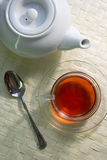 Morning tea. White teapot and glass cup on the mat Stock Photography