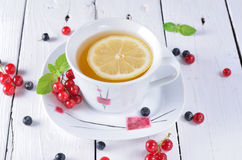 Morning tea, berries, red currants and blueberries on a white ta Stock Photography