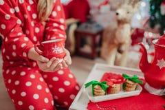 Morning tea child in red pajamas. Morning tea from a red cup of tea and a child in red pajamas Stock Image